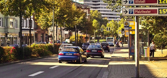 You look the Rudolf-Breitscheid-road down towards the town hall. There are several cars and a bus on this road with a green traffic light. Directly in front of the viewer is a bus stop.