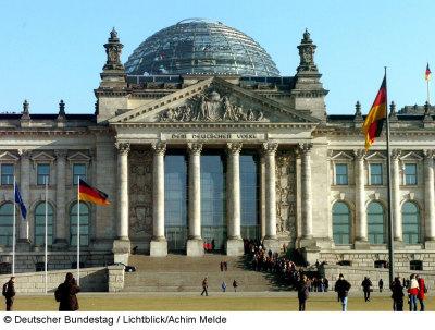 Der Deutsche Bundestag von vorne. Man kann gut die Menschenschlage erkennen, die darauf wartet in das Gebäude eingelassen zu werden.